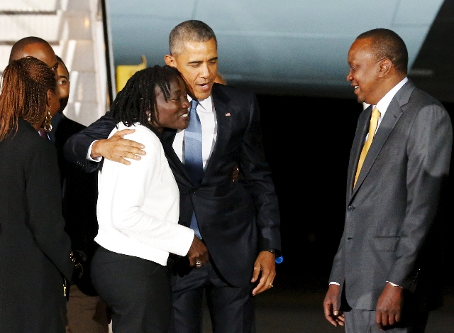 President Barack Obama embraces his half-sister Auma Obama and is greeted by Kenya's President Uhuru Kenyatta as he arrives aboard Air Force One at Jomo Kenyatta International Airport in Nai ...