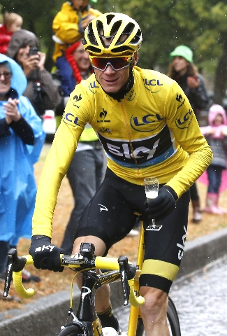Team Sky rider Chris Froome of Britain, the race overall leader's yellow jersey, holds a glass of champagne as he cycles during the 109.5-km (68 miles) final  21st stage of the 102nd Tour de ...