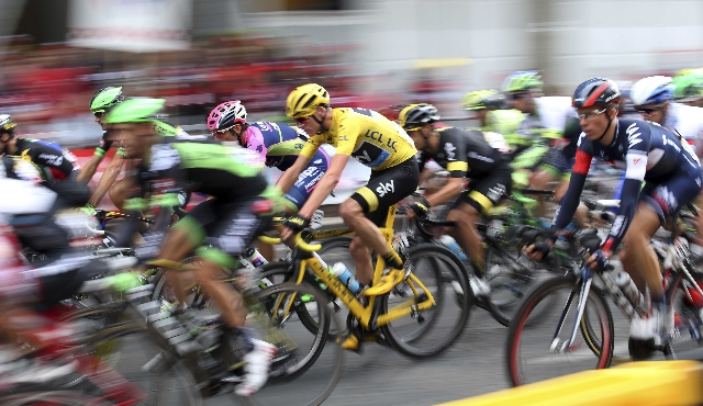 Team Sky rider Chris Froome of Britain (C), the race leader's yellow jersey, cycles on the Champs-Elysees avenue during the 109.5-km (68 miles) final 21st stage of the 102nd Tour de France c ...