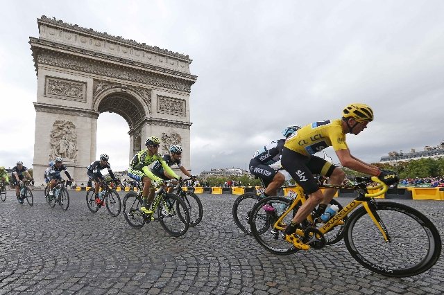 Team Sky rider Chris Froome of Britain (R), the race leader's yellow jersey, cycles near the Arc de Triomphe during the 109.5-km (68 miles) final 21st stage of the 102nd Tour de France cycli ...