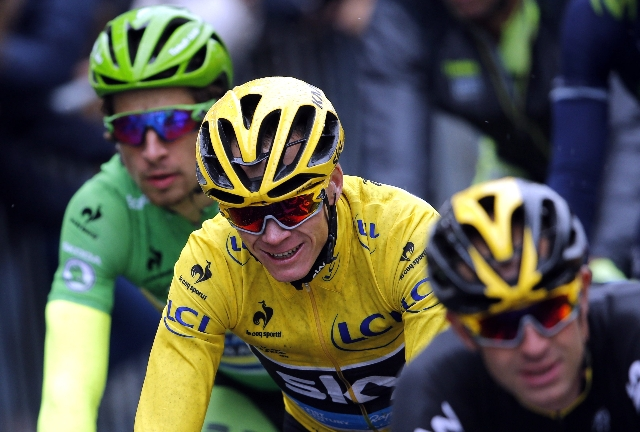 Team Sky rider Chris Froome of Britain, the race leader's yellow jersey, reacts as he cycles on the Champs-Elysees avenue during the109.5-km (68 miles) final 21st stage of the 102nd Tour de  ...
