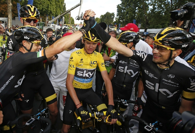 Team Sky rider Chris Froome of Britain (C), the race leader's yellow jersey, celebrates his overall victory with team-mates after the109.5-km (68 miles) final 21st stage of the 102nd Tour de ...
