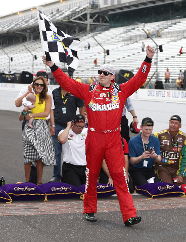 Kyle Busch waves the checkered flag after winning the Crown Royal 400 at Indianapolis Motor Speedway on Sunday. (Brian Spurlock/USA Today)