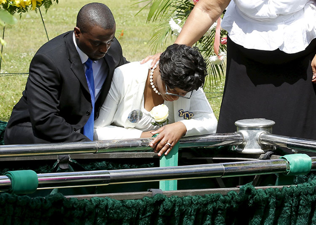 Sharon Cooper, right, sister of Sandra Bland, kneels over the burial plot of her sister Sandra Bland during the funeral in the Chicago suburb of Willow Springs, Illinois, United States, July 25, 2 ...