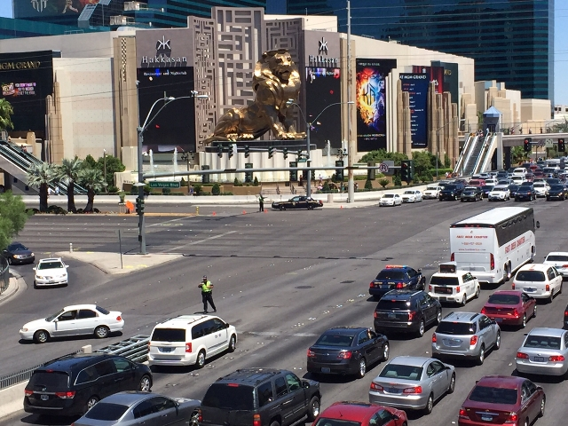 An officer directs traffic at Tropicana Avenue and the Las Vegas Strip on Saturday, July 25, 2015. A fire at The Cosmopolitan of Las Vegas has closed the Strip from Tropicana to Flamingo Road.(Cha ...