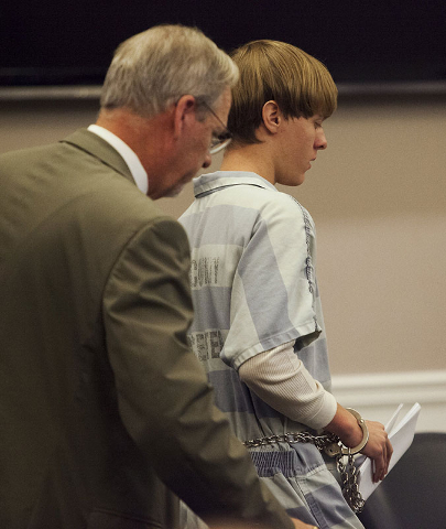 Dylann Roof, right, the 21-year-old man charged with murdering nine worshippers at a historic black church in Charleston last month, is helped to his chair by chief public defender Ashley Penningt ...