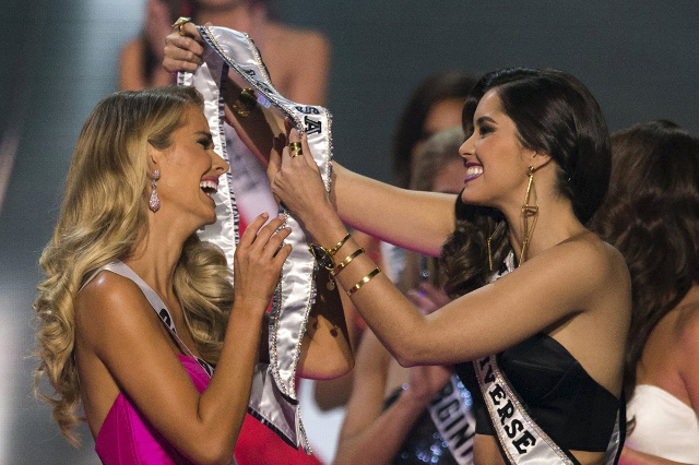 Olivia Jordan of Oklahoma (L) reacts as Miss Universe 2014 Paulina Vega of Colombia puts the winning sash around her after she won the 2015 Miss USA beauty pageant in Baton Rouge, Louisiana July 1 ...