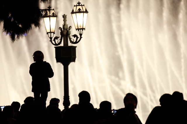 New Year's revelers watch the fountain show outside of the Bellagio hotel-casino on the Las Vegas Strip on Wednesday, Dec. 31, 2014. (Chase Stevens/Las Vegas Review-Journal)
