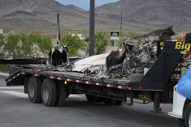 A tow truck drives away with wreckage left after a plane crash in the outskirts of Henderson near Savella Avenue and Via Firenze Avenue on Sunday, July 19, 2015. (Erik Verduzco/Las Vegas Review-Jo ...