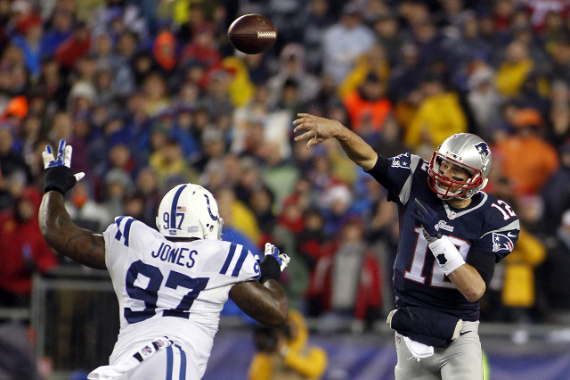 Jan 18, 2015; Foxborough, MA, USA; New England Patriots quarterback Tom Brady (12) passes the ball over Indianapolis Colts defensive end Arthur Jones (97) during the first quarter in the AFC Champ ...