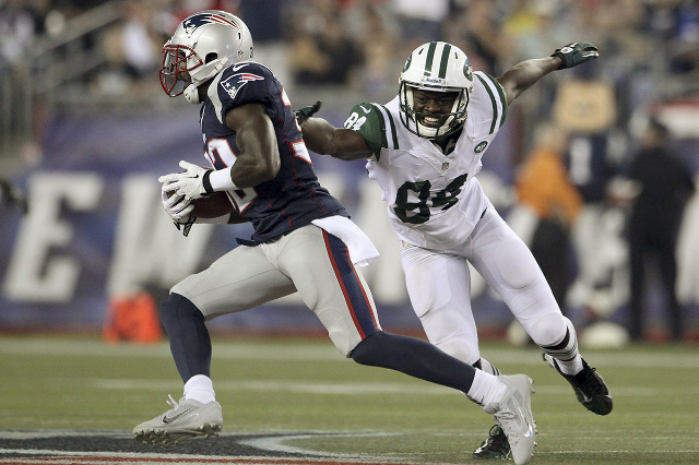 Former New York Jets wide receiver Stephen Hill tries to stop New England Patriots Devin McCourty after McCourty recovered Hill's fumble in the first quarter during their NFL AFC East footba ...
