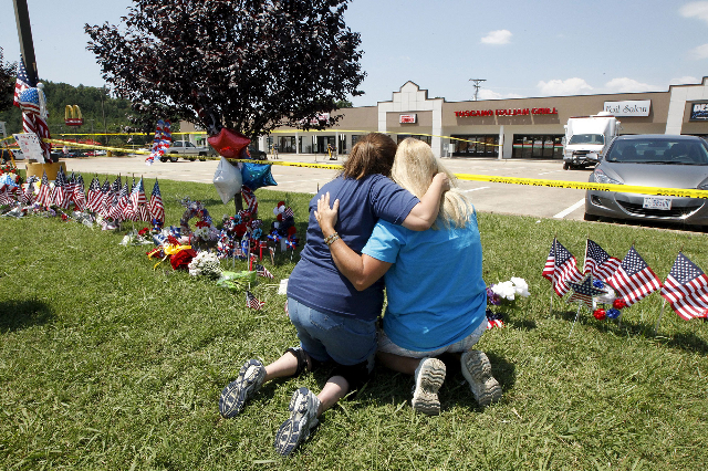 Betty Maynard, left, hugs her friend Cindy Atterton beside a growing memorial at the Armed Forces Career Center in Chattanooga, Tennessee July 17, 2015. Four U.S. Marines were killed on Thursday b ...
