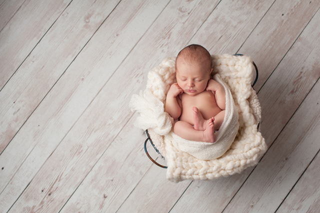 Newborn Baby Sleeping in a Wire Basket (Thinkstock)