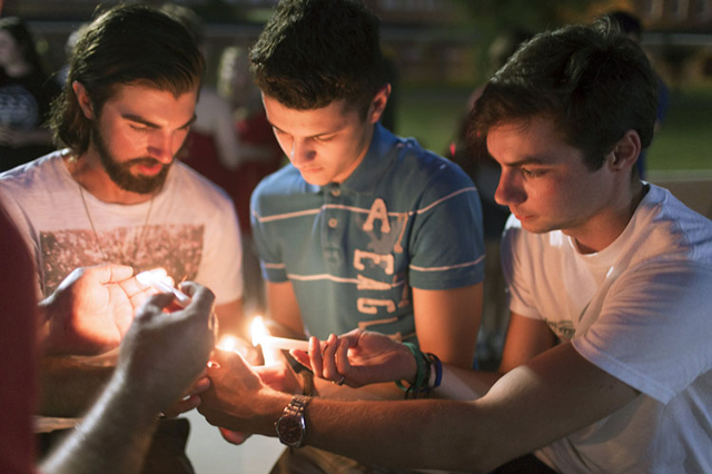 From left, Blaise Broussard, Kaleb Fry and James Smith light candles during a candlelight vigil for victims of the Thursday night shooting at a movie theater in Lafayette, La., on Friday. (Lee Cel ...