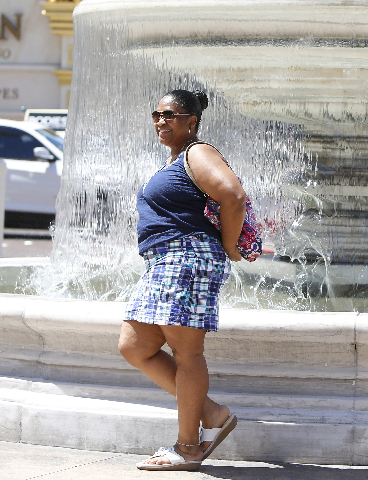 A tourist poses for a photo on a hot day near the fountain in front of the Venetian hotel-casino on Las Vegas Boulevard Wednesday, July 29, 2015. Las Vegas should hit a high of 104 degrees, about  ...