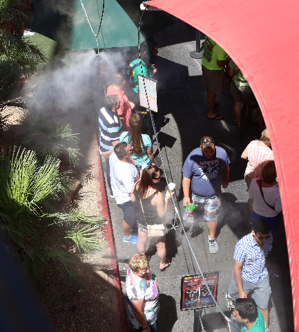 Tourists are seen through misters as they stand in line on a hot day to buy show tickets at TIX 4TONIGHT on Las Vegas Boulevard near the Venetian hotel-casino Wednesday, July 29, 2015. Las Vegas s ...