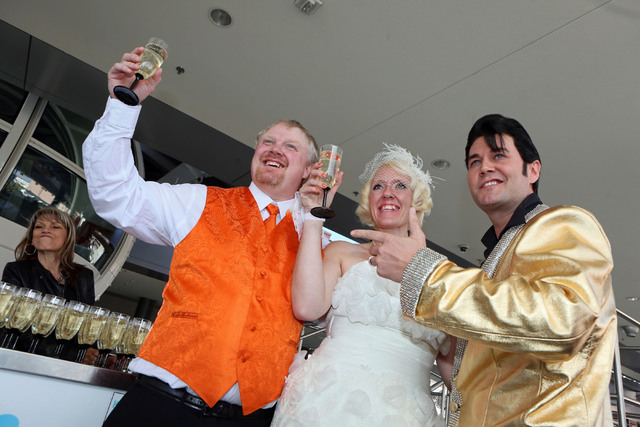 Jeremy Cardon, from left, and his bride Angel Dodson, of Colorado Springs, raise champagne glasses for a photograph with officiant Travis Allen, who is dressed as Elvis, after getting married on T ...