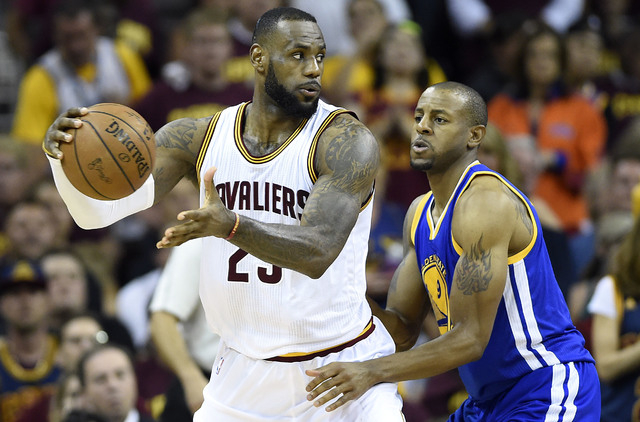 Jun 16, 2015; Cleveland, OH, USA; Cleveland Cavaliers forward LeBron James (23) handles the ball against Golden State Warriors guard Andre Iguodala (9) during the fourth quarter in game six of the ...