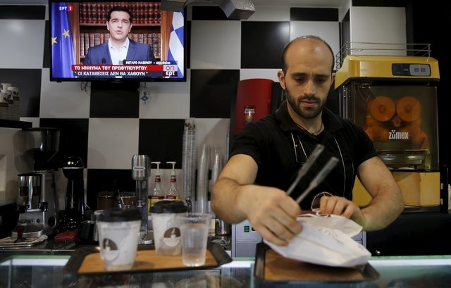 A waiter prepares coffee at a shop as the image of Greek Prime Minister Alexis Tsipras is seen live on television during a television address in Athens, Greece, July 1, 2015. Tsipras called on Gre ...