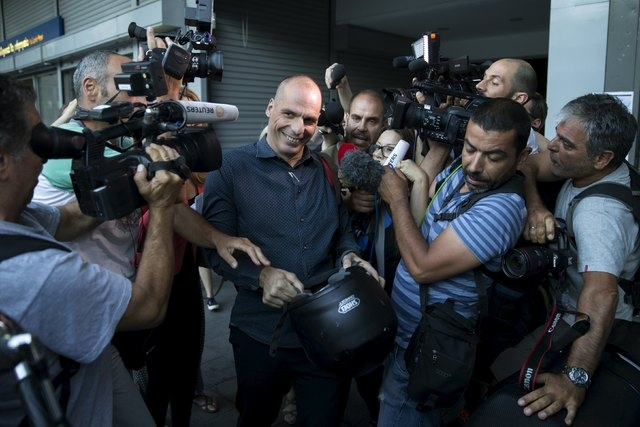 Greek Finance Minister Yanis Varoufakis is surrounded by members of the media as he leaves Finance Ministry building in Athens, Greece, July 1, 2015. A defiant Prime Minister Alexis Tsipras urged  ...
