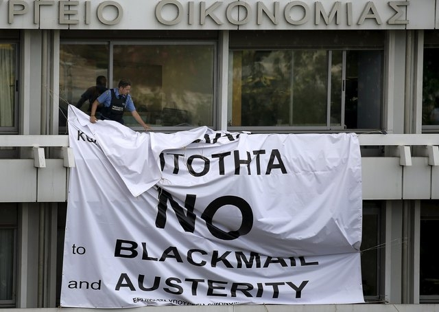 A security guard removes a banner placed earlier by protesters from a balcony of the Finance Ministry in Athens, Greece, July 1, 2015. (Reuters/Yannis Behrakis)