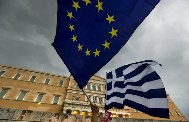 Protesters wave Greek and EU flags during a pro-Euro rally in front of the parliament building, in Athens, Greece, June 30, 2015.  (Reuters/Yannis Behrakis)