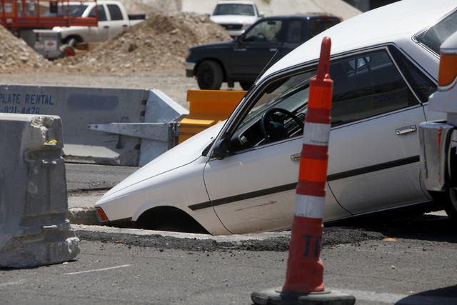 A driver drove their car into a street construction area and ended up in a hole in the 1100 block of Bonanza Road on Wednesday afternoon, July 1, 2015, in Las Vegas. (James Tensuan/Las Vegas-Revie ...