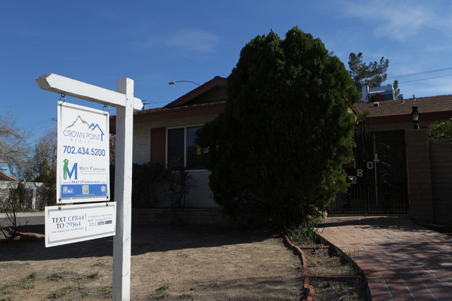 A real estate sign is posted on the lawn of a house for sale in Las Vegas. (Erik Verduzco/Las Vegas Review-Journal)