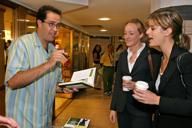 """Jared Fogle signs a copy of his book """"Jared, The Subway Guy"""" for Alex Moser, center, and Gigi Garmendia outside a Subway Restaurant in Rockefeller Center, New York City, Aug. 21, 2006. (Reuters/Su ..."""