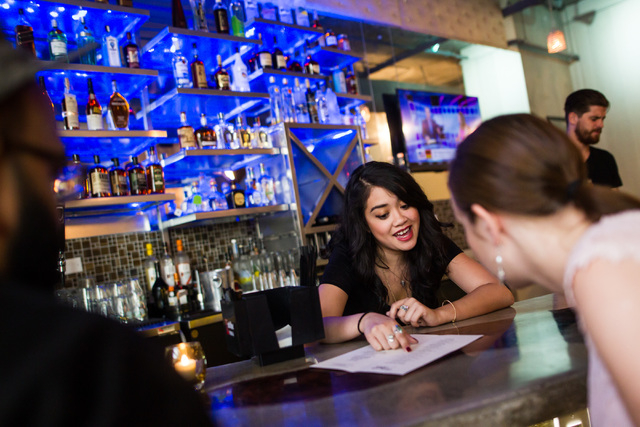 Justine Galutera, center, points out menu items to Zoneil Maharaj, left, and Nicole Ely at Classic Jewel, a lounge with a retro Las Vegas theme, at Juhl, 353 E. Bonneville Ave., in downtown Las Ve ...