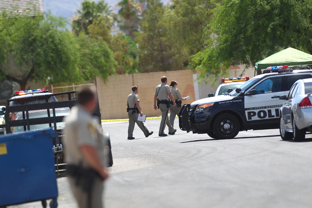 Las Vegas police investigate the scene of a shooting that left one person dead in the 3800 block of King Palm Avenue, near Alexander and Pecos roads, in Las Vegas on Tuesday, June 30, 2015. Anothe ...