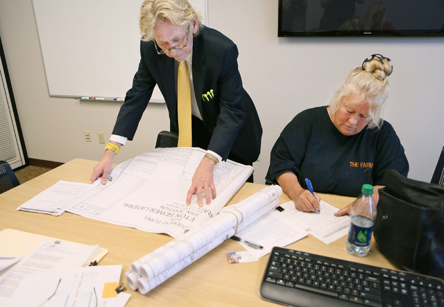 Sharon Linsenbardt, a longtime Clark County resident and owner of an animal shelter in the northwest valley, right, with the assistance of her lawyer Matthew Callister, fills out an application fo ...