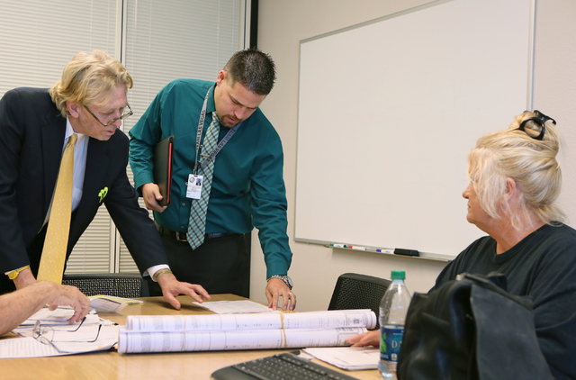 Attorney Matthew Callister, from left, and Michael Cunningham, the city's building and saftey manager, look over a form with Sharon Linsenbardt in Las Vegas on Tuesday, July 1, 2015. Sharon Linsen ...