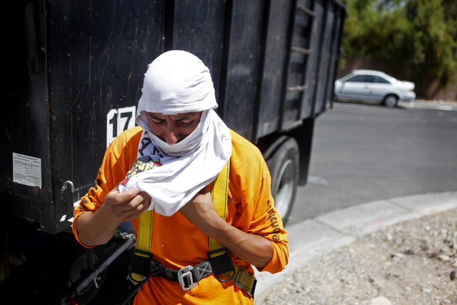 Carlos Salseda of Adaven Homes uses a shirt to mask his face and neck while he does construction work on Wednesday, July 1, 2015, in North Las Vegas. This past June was the hottest on record. (Jam ...