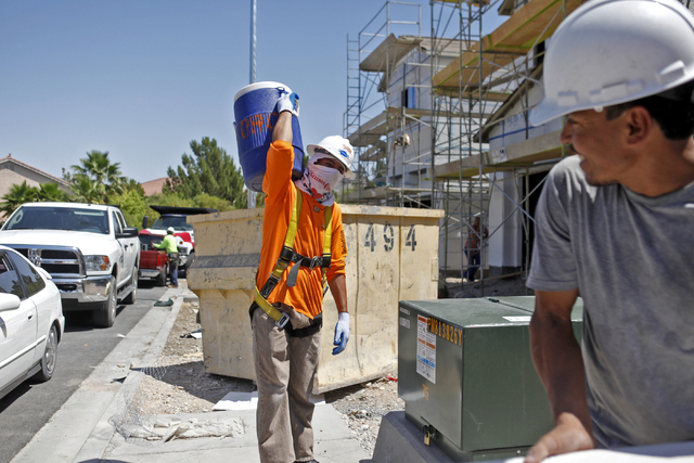 Carlos Salseda of Adaven Homes, left, carries a jug with several gallons of water on it to his construction site on Wednesday, July 1, 2015, in North Las Vegas. This past June was the hottest on r ...