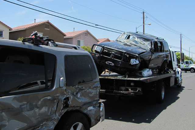 An SUV involved in a rollover crash on East Lake Mead Boulevard at Clifford Street is loaded onto a flatbed truck on Wednesday, July 1, 2015. (Greg Haas/Las Vegas Review-Journal)