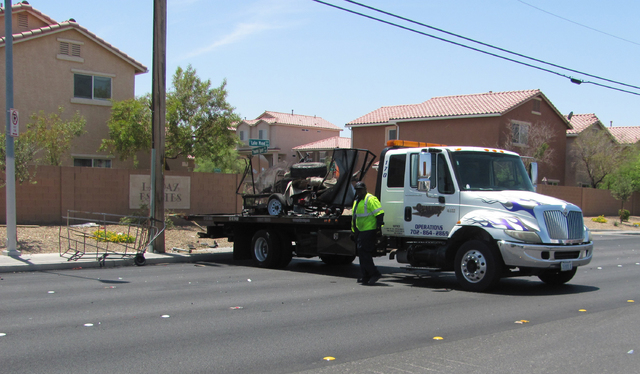 The wreckage of a utility trailer is loaded onto a flatbed truck at the scene of an accident on Lake Mead Boulevard at Clifford Street on Wednesday, July 1, 2015. (Greg Haas/Las Vegas Review-Journal)