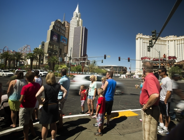 Pedestrians wait for a traffic light July 23 across the street from New York-New York. Clark County officials are concerned about traffic and parking issues associated with the arena being built b ...