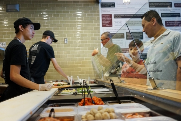 River Chair, right, orders a pizza from Jeourdin Enos, left, at Pieology in Las Vegas.   (James Tensuan/Las Vegas Review-Journal) Follow James Tensuan on twitter