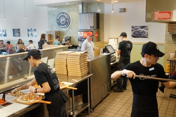 Employees at Pieology make pizzas for customers at their location in Las Vegas. (James Tensuan/Las Vegas Review-Journal) Follow James Tensuan on twitter