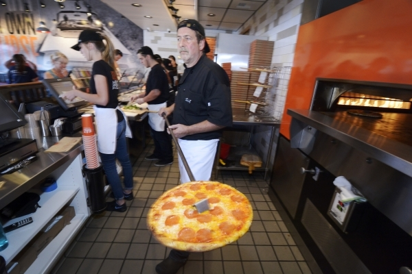 Pizza smith John LaRocca pulls a finished pie from the oven at Blaze Pizza in Henderson . (Bill Hughes/Las Vegas Review-Journal)