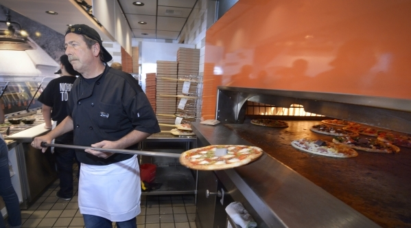 Pizza smith John LaRocca pulls a finished pie from the oven at Blaze Pizza in Henderson. (Bill Hughes/Las Vegas Review-Journal)