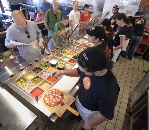 Crew members craft pizzas for customers at Blaze Pizza. Picking your favorite toppings on an individual pizza is the latest trend.(Bill Hughes/Las Vegas Review-Journal)
