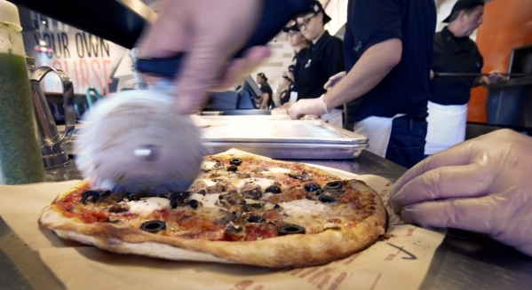 Candice Holgate slices a pie at Blaze Pizza in Henderson. (Bill Hughes/Las Vegas Review-Journal)