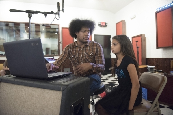 Diego Cano and Ava Thrasher, 10, review her song lyrics before recording at National Southwestern Recording. Cano is teaching children in a songwriting workshop that is part of a series of writing ...