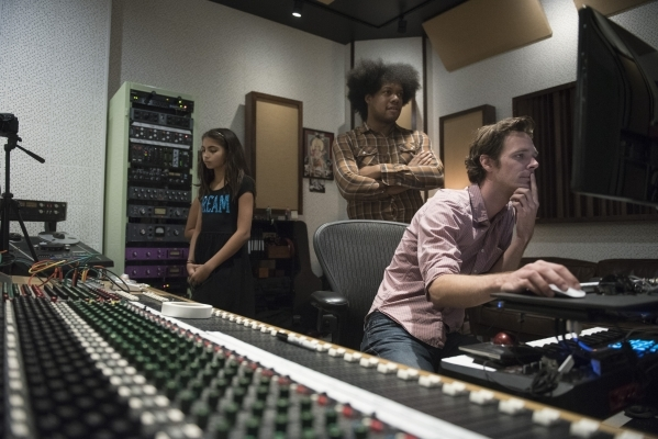 From left, Ava Thrasher, 10, Diego Cano and Mike Weller listen to a take of Thrasher's song at National Southwestern Recording. (Jason Ogulnik/Las Vegas Review-Journal)