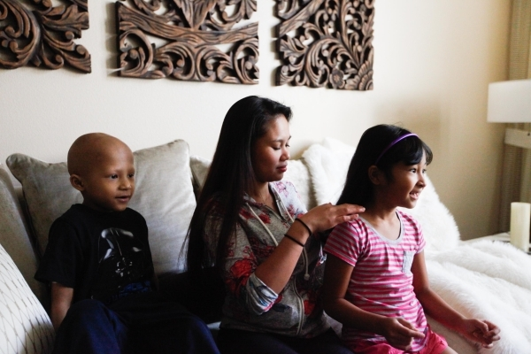 Camille de Leon fixes daughter Rosie's hair while son Anthony watches at the Ronald McDonald House. The house offers a home-away-from-home to the Reno family while Anthony receives medical t ...