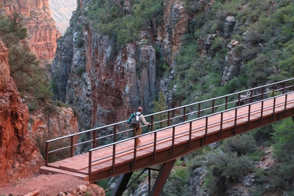 A hiker, heading down the 14-mile North Kaibab Trail to the Colorado River, crosses a bridge spanning one of the deep canyons in Grand Canyon National Park. (Deborah Wall/Special to View)