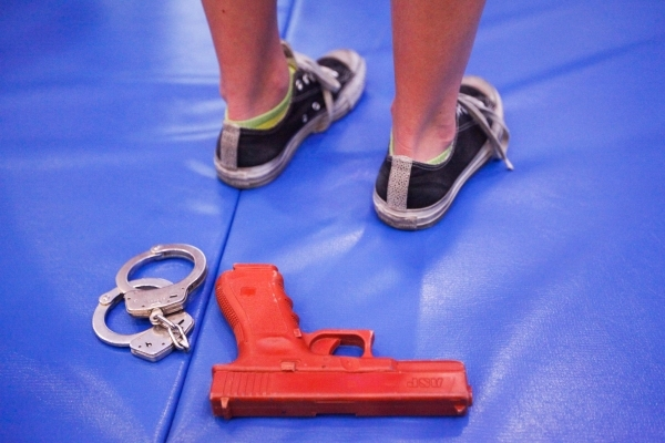 Police handcuffs and a fake gun are part of the gear young campers are given to help in their mock investigations during The Mob Museum's Secret Agents of Summer day camp. JAMES TENSUAN/LAS  ...