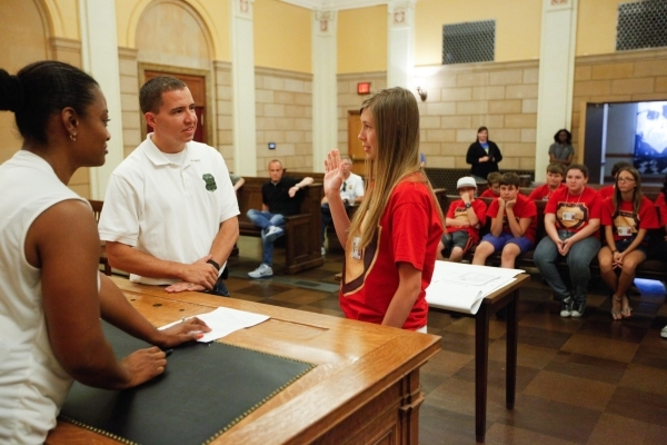 Special Agent Dave Lowe, center, helps Alexandra Vasknetz, right, appeal to a judge for a search warrant during a mock investigation as part of The Mob Museum's Secret Agents of Summer day c ...